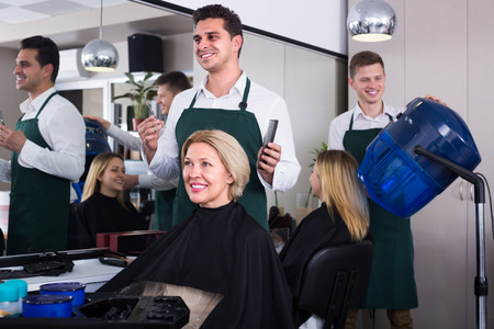 haircutter: Cheerful dark-haired man doing hairstyle for mature blonde woman in hairdressing saloon