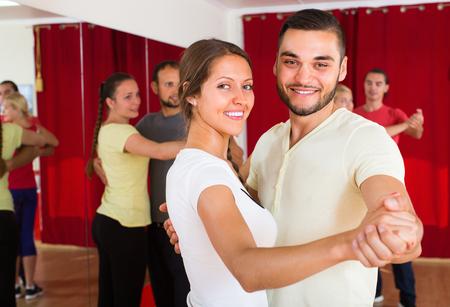 unprofessional: Smiling young men and women enjoying of partner dance in class