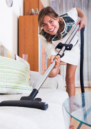 ordinary: Ordinary housewife in casual dress hoovering surfaces Stock Photo