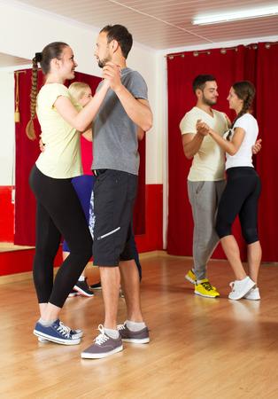 latino dance: Happy adult people dancing Latino dance in class