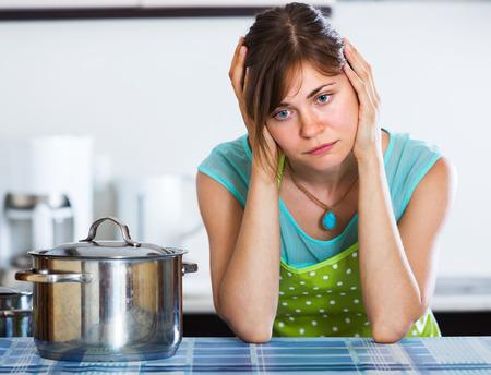 mujer triste: mujer joven con una cena cara triste de cocci�n en la cocina Foto de archivo