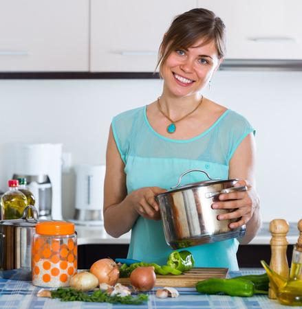 householder: Happy housewife preparing vegetables basing on new recipe indoors Stock Photo