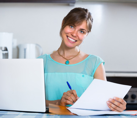 25s: Young woman filling banking documents and smiling at the kitchen