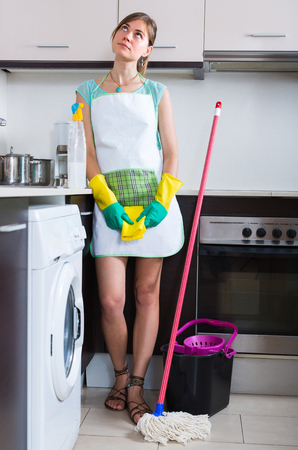 unwillingness: Portrait of young brunette girl in apron tired to clean at the kitchen