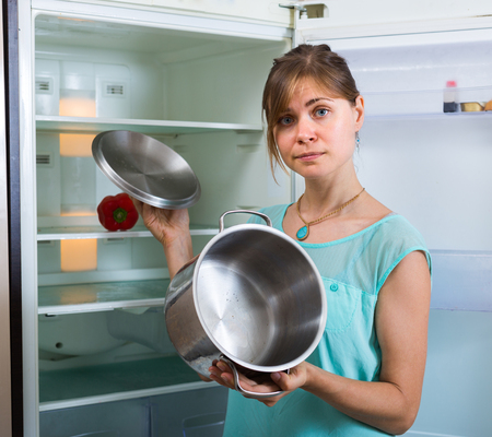 starving: Frustrated starving young woman standing near empty fridge Stock Photo