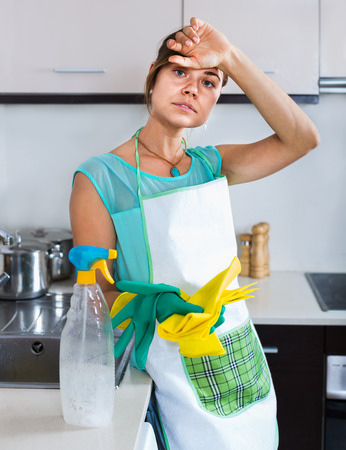 Tired young woman in rubber gloves posing at a kitchen