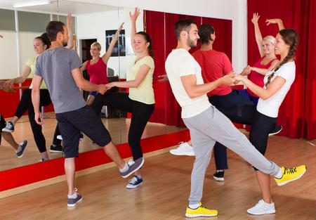 danza contemporanea: Smiling adultos jóvenes que tienen clase de baile en el estudio. Enfoque selectivo Foto de archivo