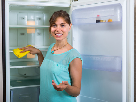 handglove: Happy young woman cleaning empty refrigerator indoors Stock Photo