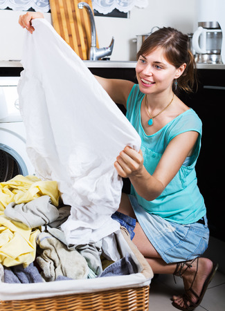 lavando ropa: Mujer contenta disfrutando de ropa limpia y sin manchas después de lavandería