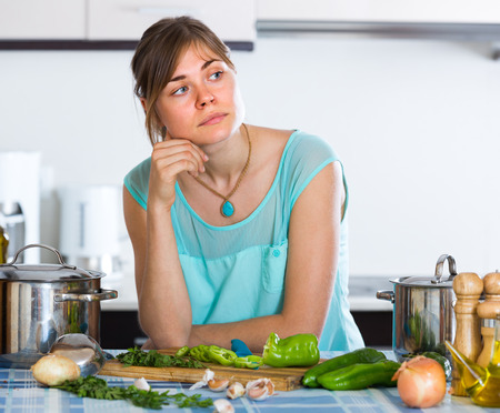 unwillingness: Portrait of sad tired young woman at home kitchen Stock Photo