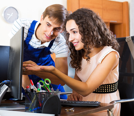 malfunction: Positive technical support engineer doing malfunction diagnosis of client computer. Focus on the woman