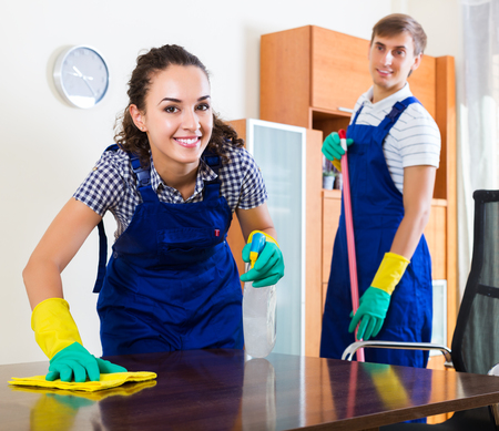 office uniform: Couple in uniform smiling and cleaning in livingroom at home