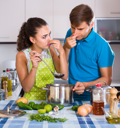 too much: Housewife put too much spices in soup, husband criticizing Stock Photo