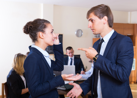lecturing: Manager lecturing mistaken team member severely at office meeting