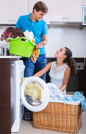 machine: Smiling young husband and wife near washing machine with basket of linen
