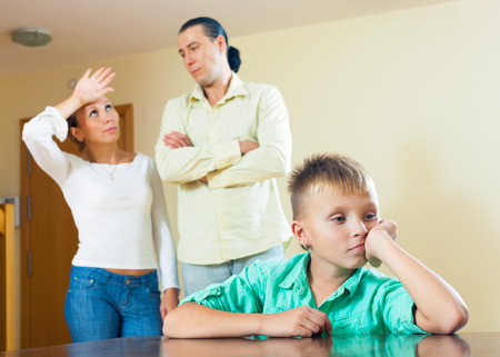 Parents and teenage son having conflict at home. Focus on boy Stock Photo