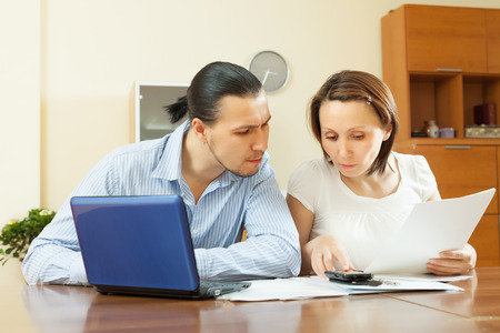 calculated: middle-aged couple calculating family budget at home interior Stock Photo