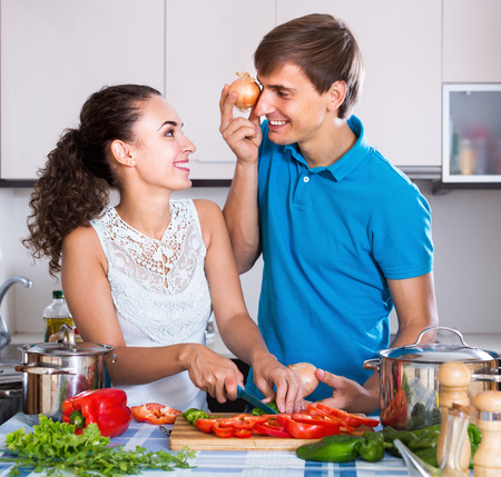 vegeterian: Smiling woman and boyfriend with vegetables preparing vegeterian soup in domestic kitchen Stock Photo