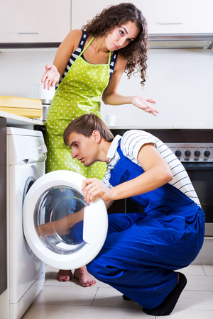 work tools: Young serviceman and sad woman standing near washing machine indoors. Focus on the man