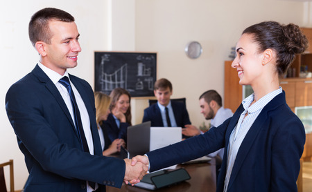 deal in: Two managers shaking hands after closing successful deal in office
