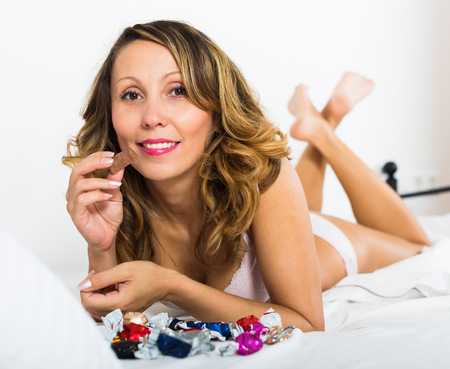 lier: Happy woman in underwear laying in bed with sweets