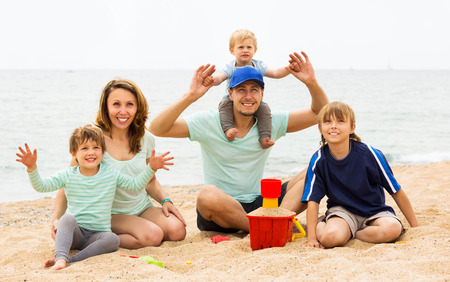 Happy parents with kids sitting at sandy beach at summer day