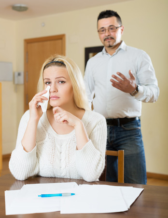 financial problems: Husband and despair wife having a financial problems at home. Focus on woman Stock Photo