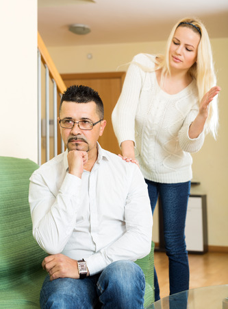 outrage: Casual couple having quarrel at home. Focus on the man