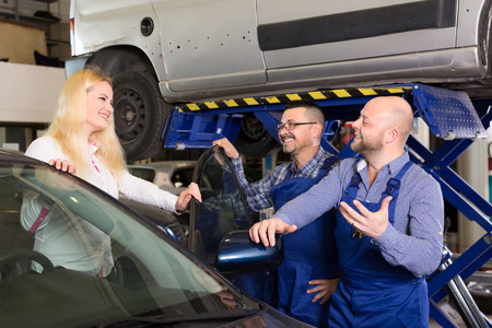 automobile workshop: Happy woman brought her car to a dealership for maintenance. Two mechanics met her indoors