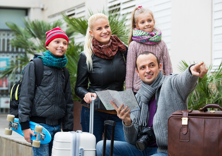 middle class: Feliz familia de clase media de cuatro miembros la comprobación de una dirección en un mapa al aire libre