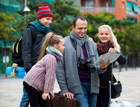 middle class: Feliz familia de clase media de cuatro personas el control de la dirección en un mapa