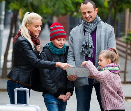 clase media: Feliz familia de clase media de cuatro miembros comprobar la direcci�n en el mapa Foto de archivo