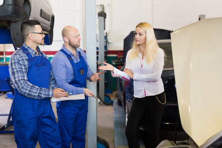 job occupation: Two mechanics trying to cheat sad female client at workshop