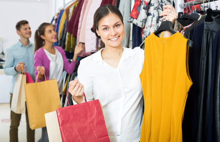 liked: Attractive young woman customers chooses liked things in the boutique