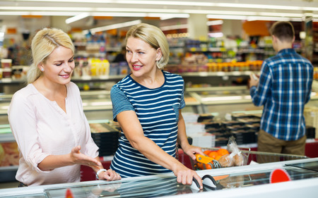 alimentos congelados: Clientes femeninas de pie cerca de la pantalla con los alimentos congelados en el supermercado Foto de archivo