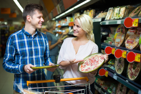 cooled: Satisfied spouses buying Italian pizza in cooled food section Stock Photo