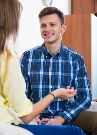talkative: Smiling young guy having positive conversation with his girlfriend indoors