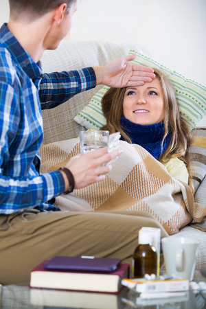 flue: Portrait of positive sick girl with flue and nursing man indoors Stock Photo