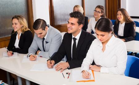 Attente volwassen studenten bedrijfskunde aan de balies in de klas. Selectieve aandacht