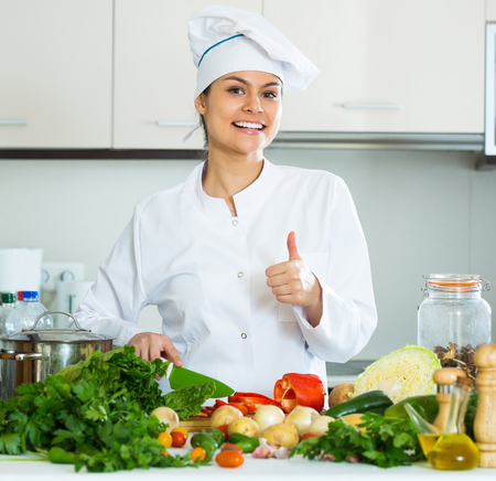 25s: Cheerful smiling girl in uniform cooking vegetables at kitchen