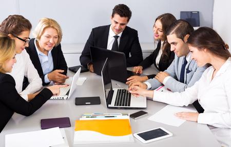 miembros positivos de las reuniones de negocios multinacionales en el trabajo en la oficina. Centrarse en el hombre y la mujer adecuada Foto de archivo