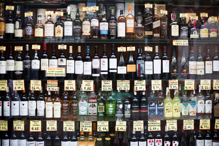 BARCELONA, SPAIN - OCTOBER 27, 2015: View at glass display of ordinary liquor store with alcoholic beverages in bottles