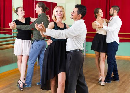 tango: Three smiling young couples dancing tango in dancing studio. Selective focus