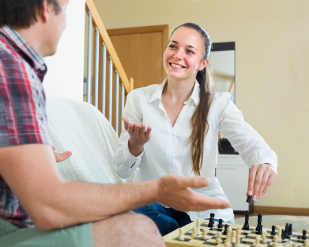 boy room: Relaxed young european couple playing chess at home sitting on the sofa Stock Photo