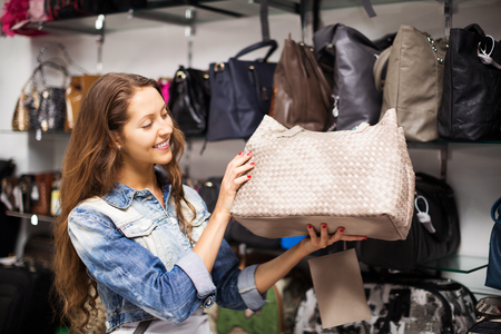 leather bag: Smiling woman choosing leather bag in shop Stock Photo