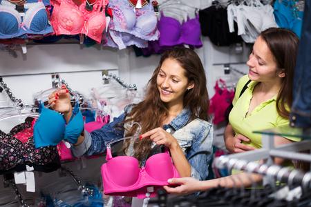 underclothing: Two young women shoppers choosing underwear in shop