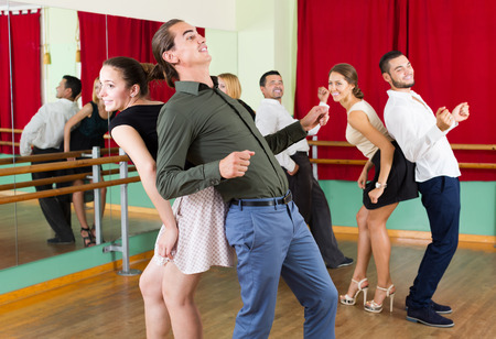 merry dancers: Tree happy couples dancing rock-and-roll in dancing-class