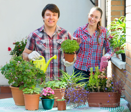 foliar: Young cheerful smiling people florists working at the garden Stock Photo