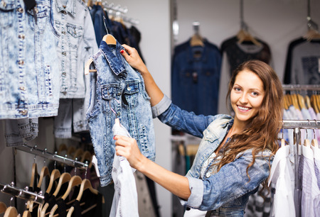 Young happy girl buying denim vest in clothing store