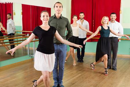 merry dancers: Tree  young beautiful couples dancing waltz in dancing-class